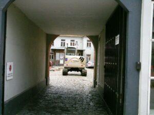 Minigraver gennem portåbning til baggården