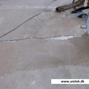 Revne i gulvet skåret op og løs beton er fjernet forud for fugning med epoxy.