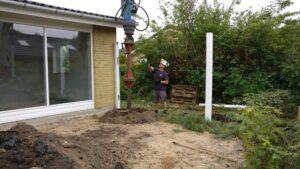 Pæl bores på hjørne af hus hvor tilbygning skal starte