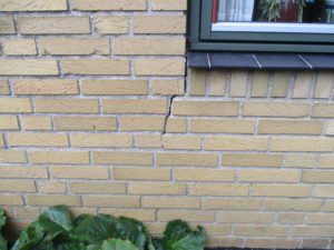 Revne i mur under vindue inden stabilisering med skruepæle